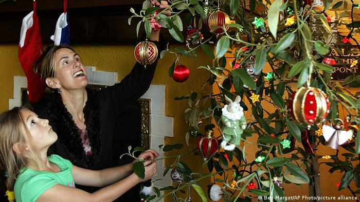 A mother and daughter decorate a primrose tree
