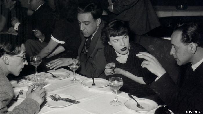 Paul Celan und Ingeborg Bachmann sitzen an einem Esstisch und unterhalten sich, Celan hält eine Zigarette in der Hand.