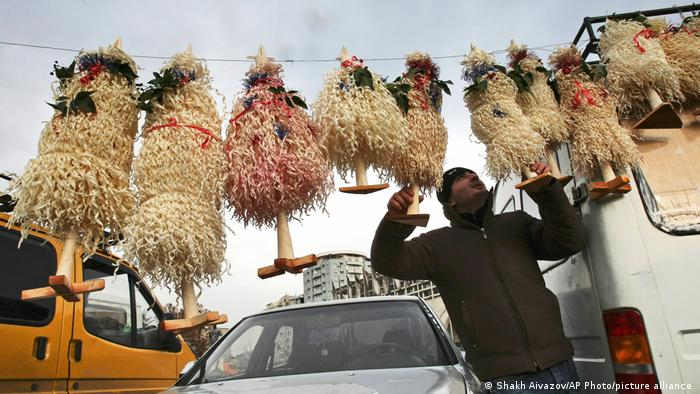 A man holds up traditional Georgian Christmas trees made of shaved hazlenut wood