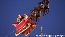 BERLIN, GERMANY - NOVEMBER 25: An actor dressed as Santa Claus waves from a suspended sleigh over a Christmas market as the Dom cathedral stands behind on November 25, 2013 in Berlin, Germany. Christmas markets, which traditionally sell mulled wine, stollen cake, Christmas tree ornaments and other crafts and are an essential part of German Christmas tradition, open across the country this week. (Photo by Sean Gallup/Getty Images)