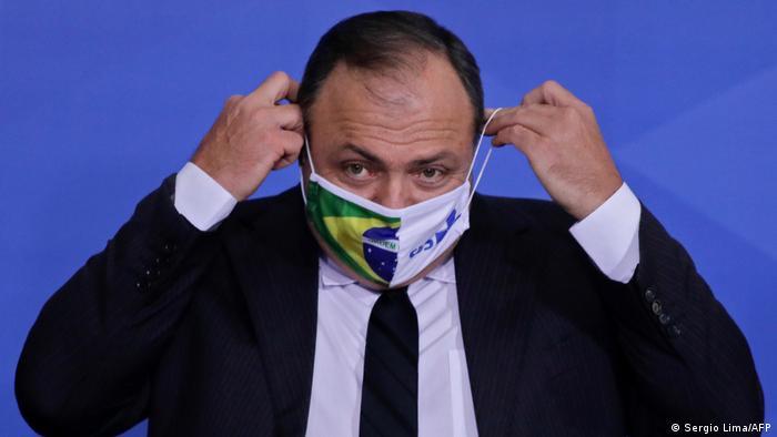 Former health minister Eduardo Pazuello puts on mask.