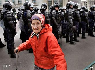 An elderly woman passes by a line of special riot police officers in Bucharest, Romania.