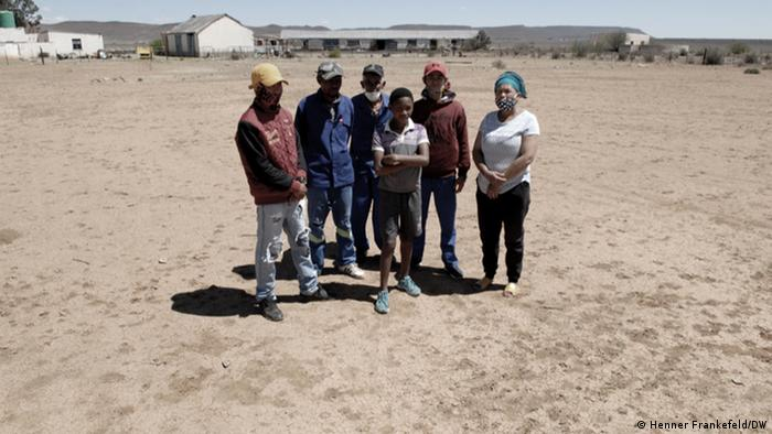 Six people stand in a dry field in the sun