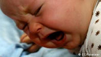 Ein Baby liegt weinend auf einem Kissen