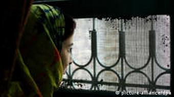 A woman looks out a barred window
