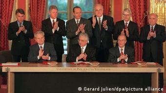 Οι ειρηνοποιοί και πρώην πολέμαρχοι χειροκροτούν μετά την υπογραφή της συμφωνίας του Ντέιτον το 1995 στο Παρίσι