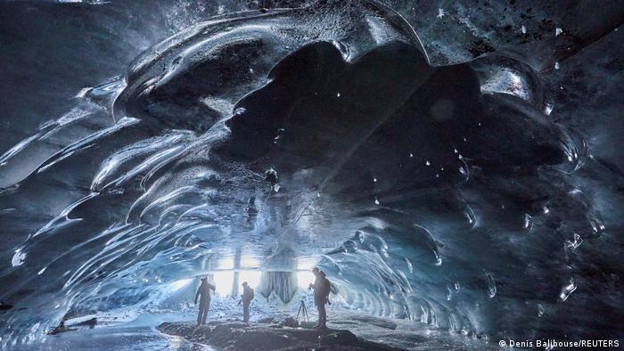 """Ljudi u """"Mlinu"""", prirodnoj, ledenoj pećini dugoj 20 metara na skijalištu Les Diablerets – Glacier 3000 u Švajcarskoj. Voda koja se tu tokom leta otapa, na jesen formira ovu ledenu kupolu."""
