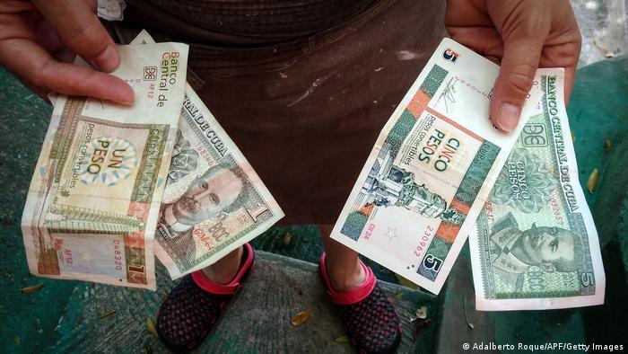 Eine Person hält in den Händen verschiedene Geldscheine
