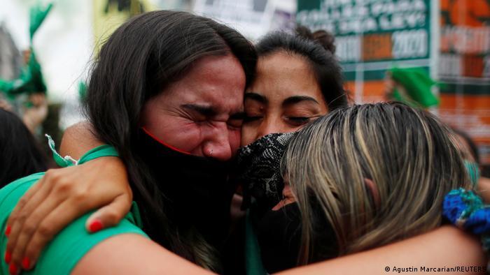 Tres mujeres vestidas de verde y con pañuelos verdes se abrazan, llorando, para celebrar la aprobación en Diputados de la ley sobre el aborto legal y seguro.