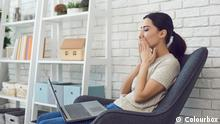 Young brunette woman sitting on armchair and kissing virtual interlocutor on laptop screen during online meeting, side view. Online communication concept