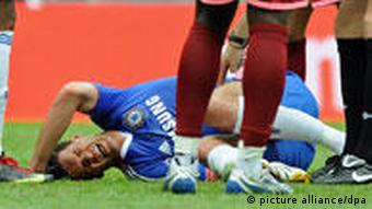 Ballack writhes on the ground after picking up his ankle injury.