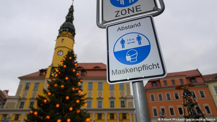 A sign advising people to wear face masks near a Christmas tree in Bautzen