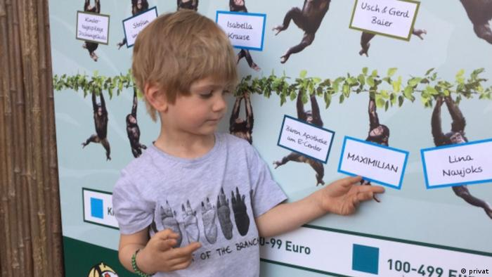 six year old Maximilian pointing to a board showing chimpanzees and donors' names