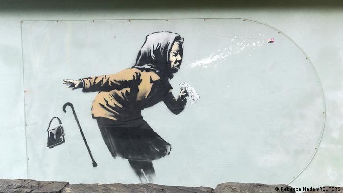 پاندمی کرونا الهامبخش بنسکی، هنرمند معروف خیابانی نیز بود که اوایل ماه دسامبر با این تصویر خبرساز شد: پیرزنی که در پی عطسه نه تنها کیف و عصایش را از دست داده و ذرات آلوده به هوا میفرستند، بلکه با دندانهای عاریهاش نیز وداع میکند.