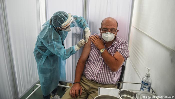 Profissional com roupa de proteção aplica injeção em homem com máscara