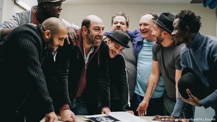 Europäischer Filmpreis: «The Big Hit» ist beste Komödie - im Filmstill stehen mehrere Männer um einen Tisch herum und strahlen