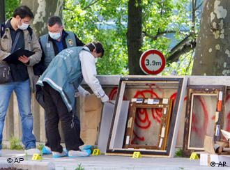Police pack up the frames of the stolen paintings
