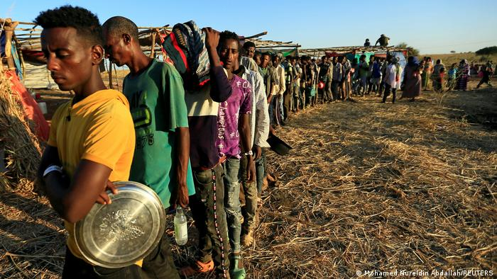 Ethiopian refugees who fled to Sudan from Tigray wait in line to receive food aid