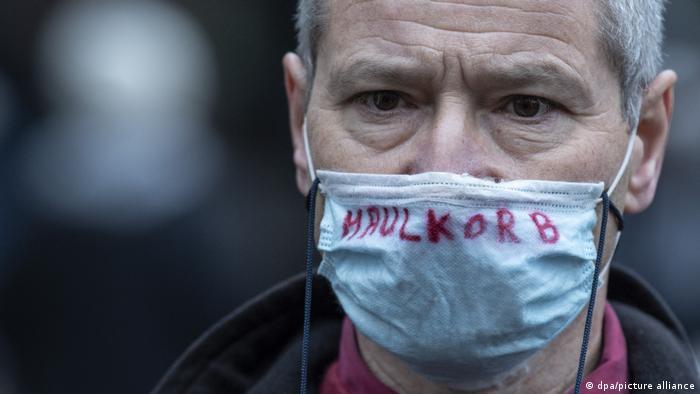 Grauhaariger Mann, der einen Mund-Nasen-Schutz mit der Aufschrift Maulkorb trägt
