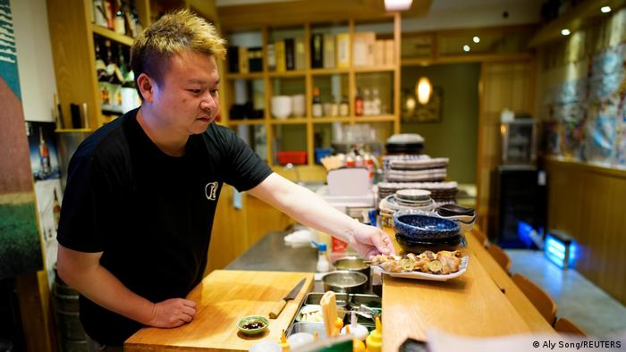 Lai Yun plates a dish at his restaurant