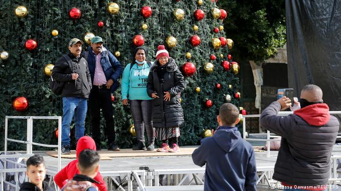مسيحيون فلسطينيون يأخذون صورا تذكارية أمام شجرة عيد الميلاد في بيت لحم