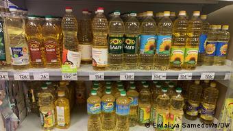На полках стоят бутылки с подсолнечным маслом