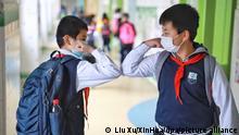 Zwei Schüler einer Grundschule grüßen sich mit ihren Ellbogen. Die Grundschulen in Guiyang nehmen den Unterricht allmählich wieder auf.