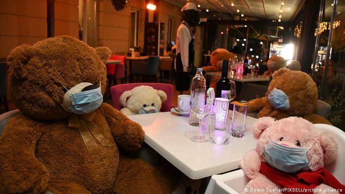 شماری از کافهها و رستورانها که پس از کاهش محدودیتها بازگشایی شدند، دست به ابتکار عملی جالب زده و دور برخی از میزها خرسهای عروسکی نشاندند تا مشتریان راحتتر بتوانند فاصلهگذاری فیزیکی را رعایت کنند. با تشدید محدودیتها رستورانها و کافهها دوباره تعطیل شدند، اما خرسها همچنان مهمان برخی از آنها هستتد، از جمله در این رستوران که غذاهای ویژه از کرواسی عرضه میکند.