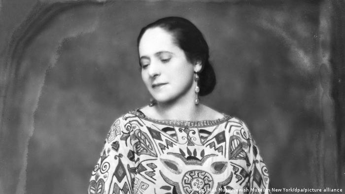 Helena Rubinstein in a striking dress, with long earrings and an aura of glamour