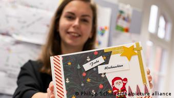 Сотрудница городской администрации держит в руках письмо с поздравлениями к Рождеству