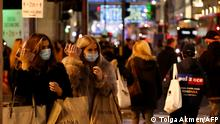 Shoppers wearing protective face coverings to combat the spread of the coronavirus, pass under the Christmas lights on Oxford Street in central London on December 14, 2020, as it is announced that Greater London will be moved into Tier 3 from Tier 2 from Wednesday December 16. - London is to move into the highest level of anti-virus restrictions, the health minister announced Monday. The British capital from Wednesday will go into tier three restrictions, which force the closure of theatres and ban people from eating out at restaurants or drinking in pubs, the Health Secretary Matt Hancock told parliament. (Photo by Tolga Akmen / AFP)