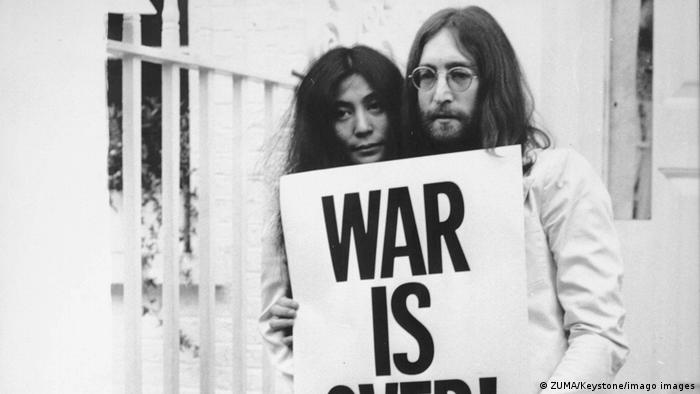 John Lennon with Yoko Ono with sign 'Was is over'