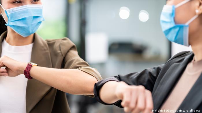Two young women wearing masks touching elbows as greeting