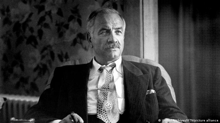 Schwarz-weiß Fotografie zeigt einen Mann mit Schnurrbart, sitzend, in Anzug und Krawatte. In der Hand hält er eine Zigarre.