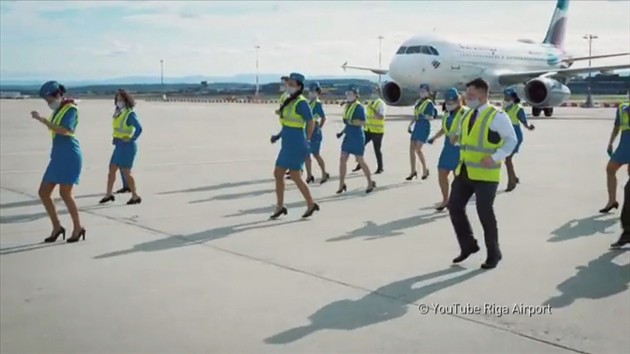 Flight crew recording a video for the Jerusalema challenge, dancing in a group in front of a plane on the tarmac at Riga Airport.