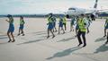 Mehrere Menschen mit gelben Westen tanzen vor einem Flugzeug.