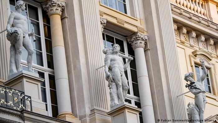 Three classical style statues by a historic-looking building.