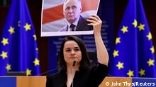 Sviatlana Tsikhanouskaya hold up a photo of political prisoner Mikola Statkevich
