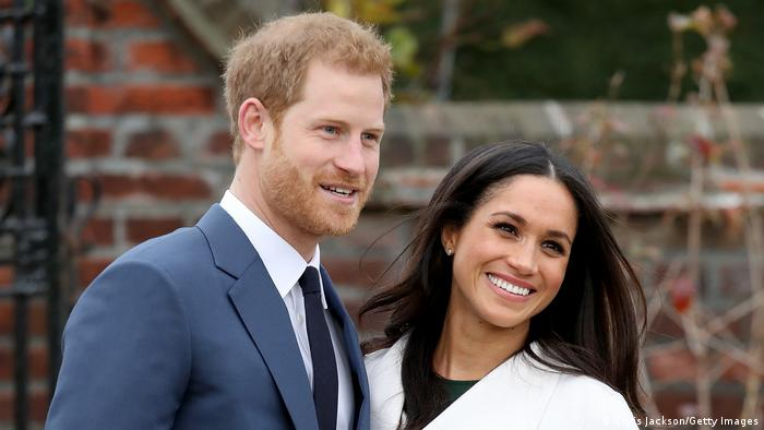 Prince Harry and Meghan Markle smiling in front of a brick wall outside.