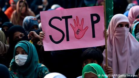 A supporter of Pakistani Islamic political party Jamaat-e-Islami (JI) holds a placard reading Stop during a protest against an alleged gang rape of a woman
