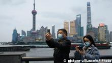 Two people wearing masks and using their phone in Shanghai, China