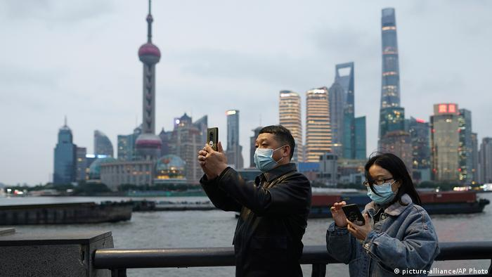 Chineses em frente a uma cidade