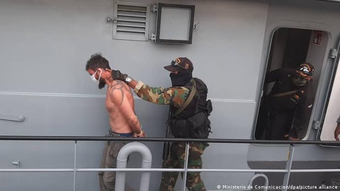 Un soldado lleva detenido a un hombre en Macuto, Venezuela.
