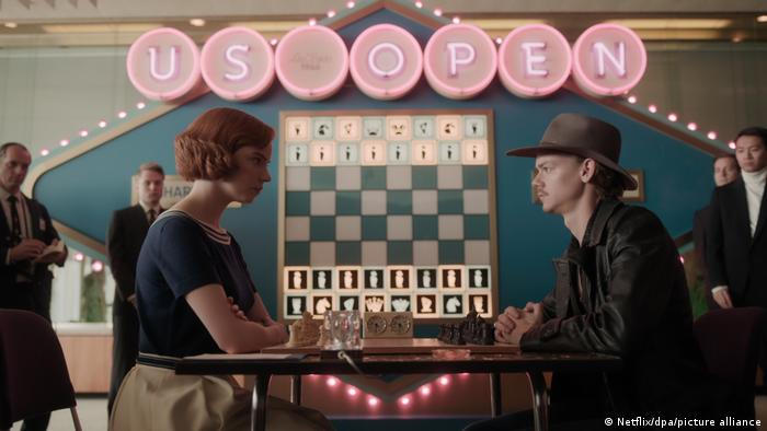 Film still the Queen's Gambit, a man and a woman seated at a table playing chess, a neon sign in the background reads US OPEN