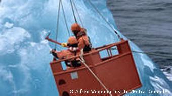 An einem Auslegerkran schweben Besatzungsmitglieder der Polarstern