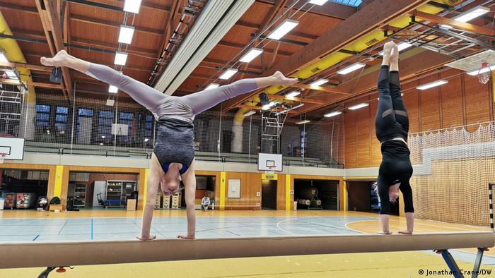 Die Turnerinnen Naomi und Ruby von Dijk machen einen Handstand auf einem Schwebebalken.