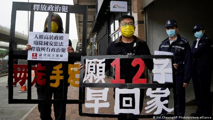 Pro-democracy activists Leung Kwok-hung, left, and Raphael Wong Ho-ming holding placards, march to the Chinese central government's liaison office