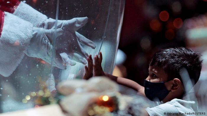 Djed Mraz u plastičnoj kugli koju dodiruje dijete