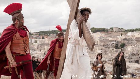 Film still The New Gospel, a man carrying a huge wooden cross accompanied by a Roman sodier