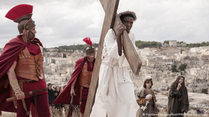 Filmstill aus Das neue Evangelium: Ein Mann trägt als Jesus verkleidet ein Kreuz, beobachtet von römischen Soldaten und zwei Frauen